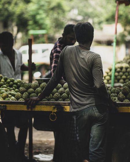 Rear view of men at market stall