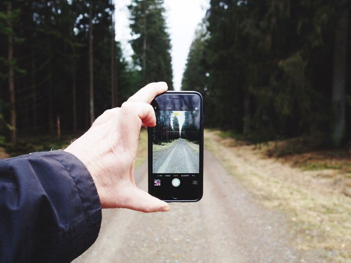 Close-Up Of Man Using Mobile Phone In Forest