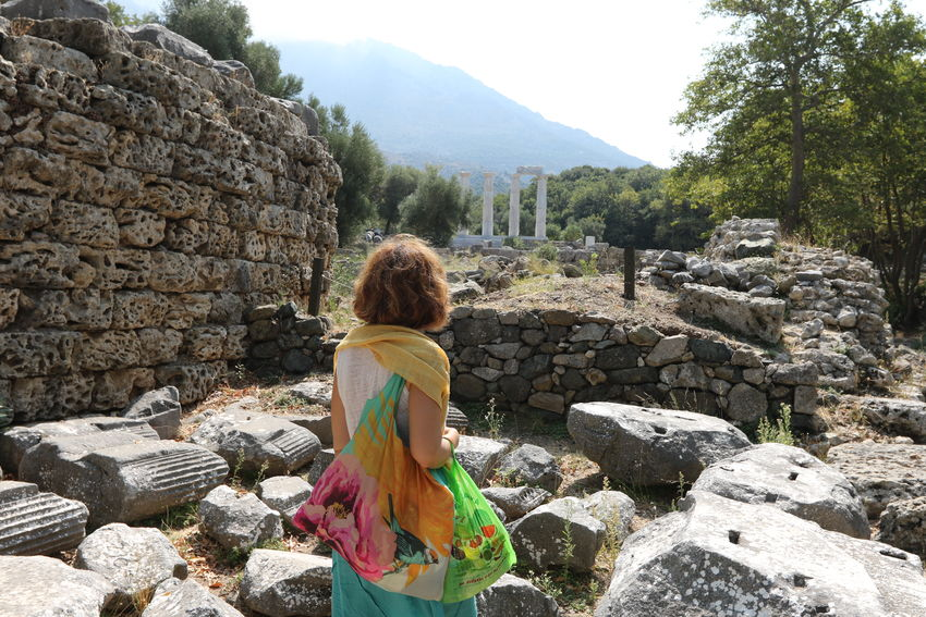 View of woman walking in the ancient ruins of the Sanctuary of the Great Gods in Samothrace, Aegean islands, East Macedonia and Thrace, Greece. Ancient Greece Ancient Ruins Architecture Beauty In Nature Building Exterior Built Structure Casual Clothing Day Leisure Activity Lifestyles Mountain Nature One Person Outdoors Real People Rear View Rock - Object Ruin Samothrace Sky Standing Temple Touristic Destination Tree Young Adult