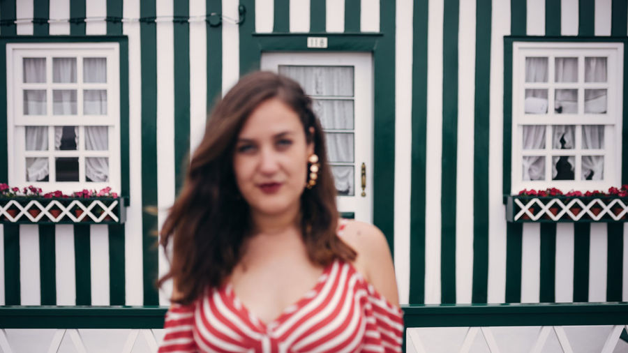 Portrait of beautiful woman standing against striped building with focus on the background