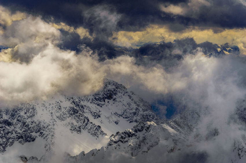 View to snow-capped Mountains sorrounded by dramatic Clouds. Berge Glacier Weather Mountains 冬の景色 Ominous Alpine Calmness Nature Winter Atmospheric Backgrounds Cloud - Sky Cloudscape Cold Temperature Environment Landscape Majestic Mountain Mountain Peak Mountain Range No People Non-urban Scene Scenics - Nature Sky Snow Snowcapped Mountain Tranquil Scene Tranquility White Color