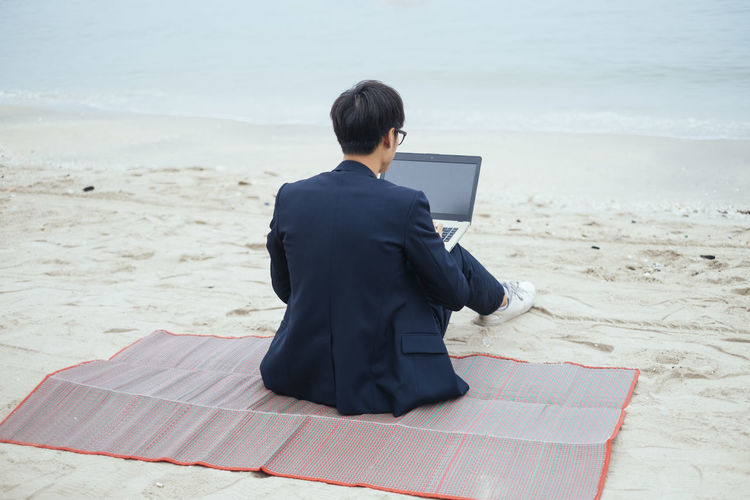 Rear view of man sitting on beach