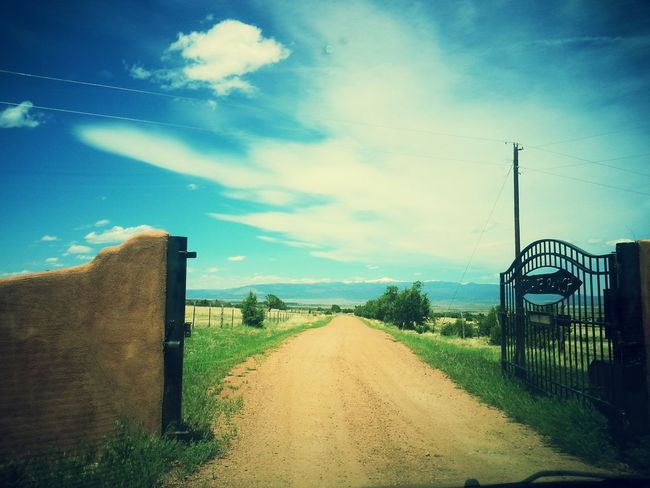 The Essence Of Summer Aneye4theshot Colorado Ranch Dirt Road Green Grass Gate Fence Sky And Clouds Mountains