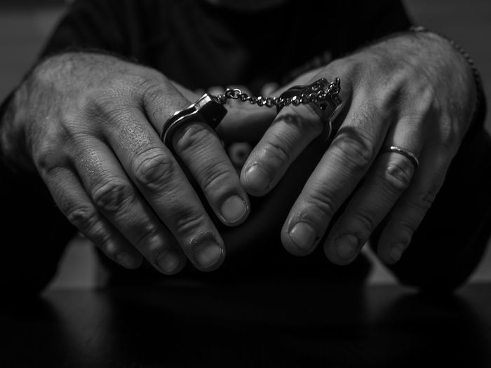 A man handcuffed with small handcuffs