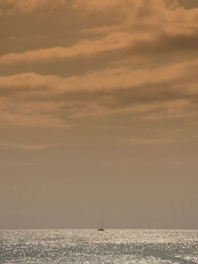 Distant ship on calm sea at sunset