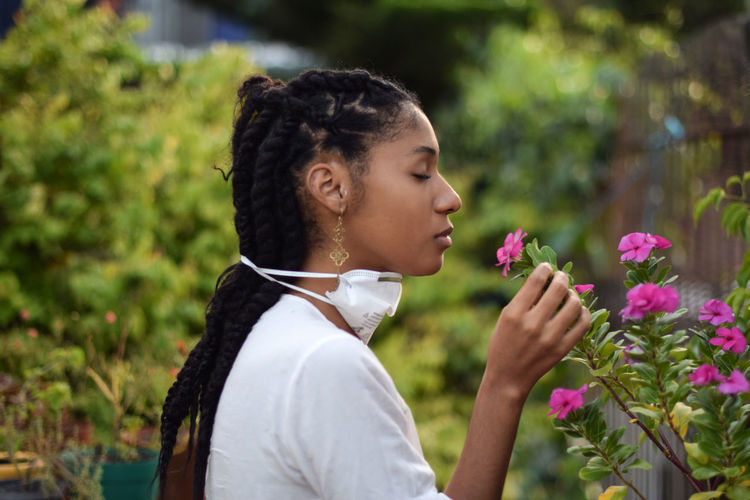 Side view of teenage girl holding flowering plant