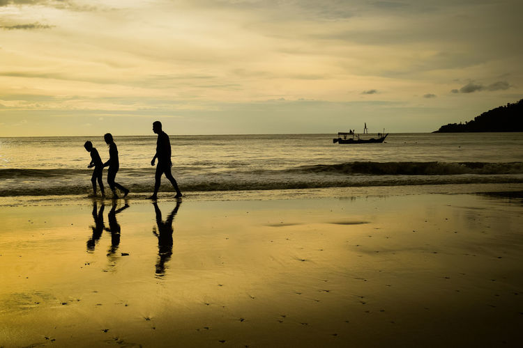 Friends Walking At Beach Against Sky During Sunset