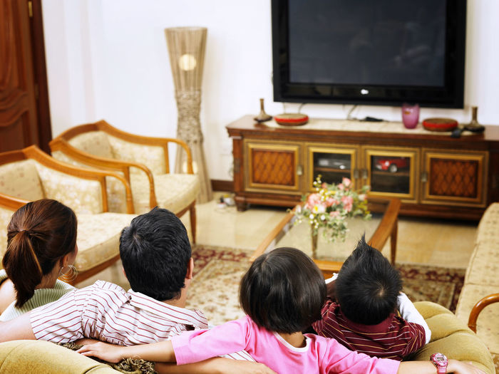 real view of parent with two kids at home watching tv Asian Family At Home Family Happiness Happy Love Bonding Cheerful Childhood Domestic Life Elementary Age Enjoyment Family Time Group Of People Leisure Activity Lifestyles Parent With Kids Parenting Real People Rear View Simple Life Sitting Smile Togetherness Watching Tv
