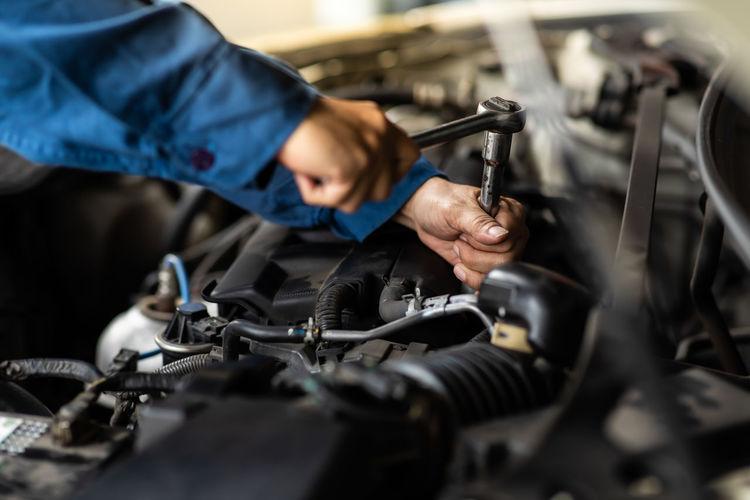 Close-up of man repairing car at workshop