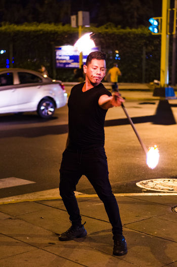 Full length of man performing with fire on street at night