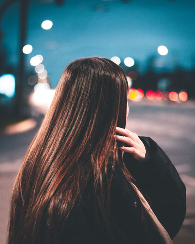 Woman standing in city at night