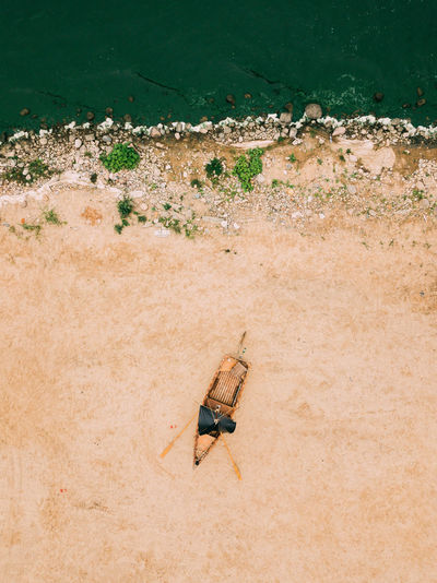 Aerial view of old boat on the sandy shore