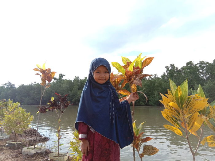 Portrait of girl in hijab standing by plants against lake