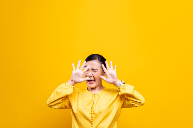 Woman showing stop gesture while standing against yellow background