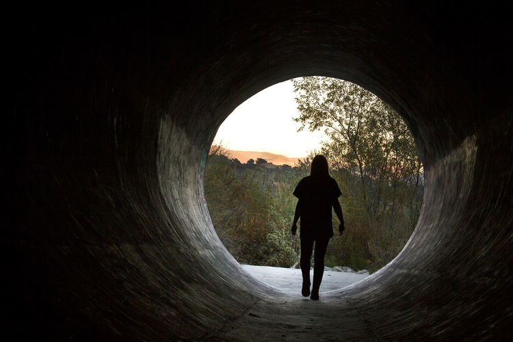 Silhouette Real People Standing Tree Light At The End Of The Tunnel Outdoors Walking Arch Leisure Activity One Person Day Tunnel
