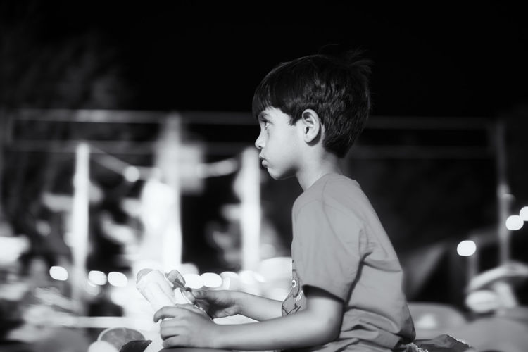 Side view of thoughtful boy sitting against sky at night