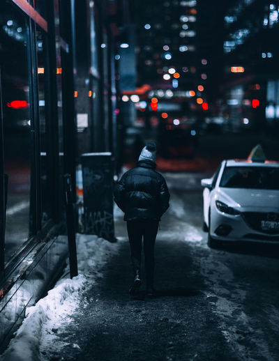 Rear view of man standing on snow covered street at night