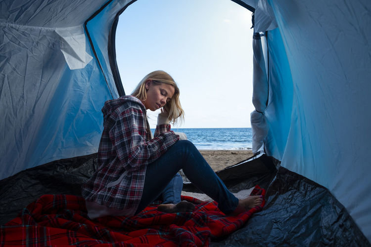 Woman sitting in tent at beach against sea and sky