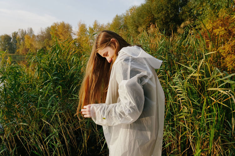 Young Adult Young Women Long Hair Hairstyle Hair Outdoors Beautiful Woman Leisure Activity Lifestyles Nature Nature Nature Photography Girl Raincoat Redhead Red Hair Beautiful Autumn Autumn colors Trees Green Plant Plants Reed Reed - Grass Family Sunlight