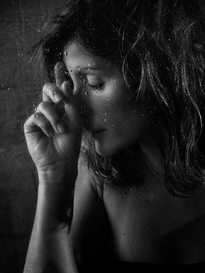 Close-Up Of Woman Seen Through Wet Window