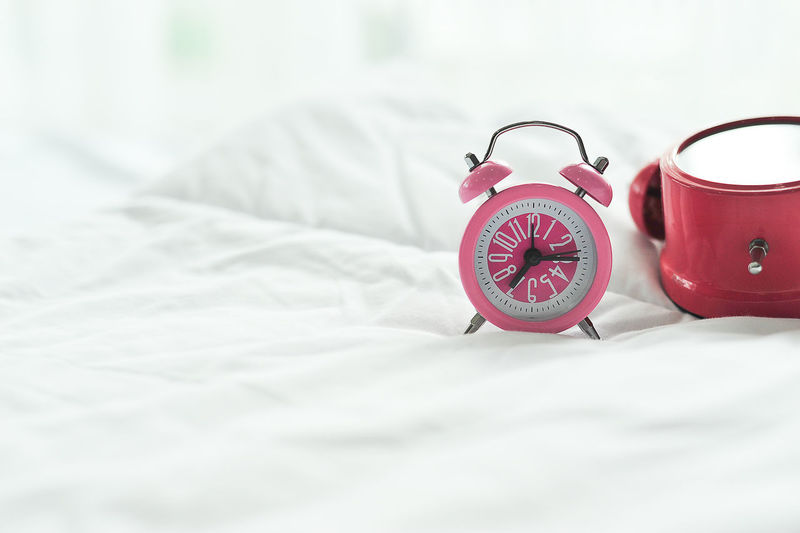 Absence Alarm Clock Bed Bedroom Clock Close-up Domestic Room Focus On Foreground Furniture Indoors  Linen No People Pattern Pink Color Red Selective Focus Sheet Still Life Textile White Color