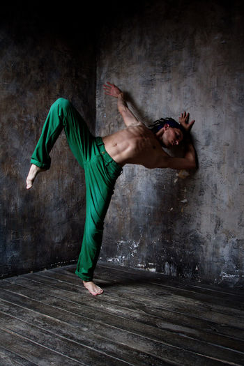 Full length of young man dancing against wall