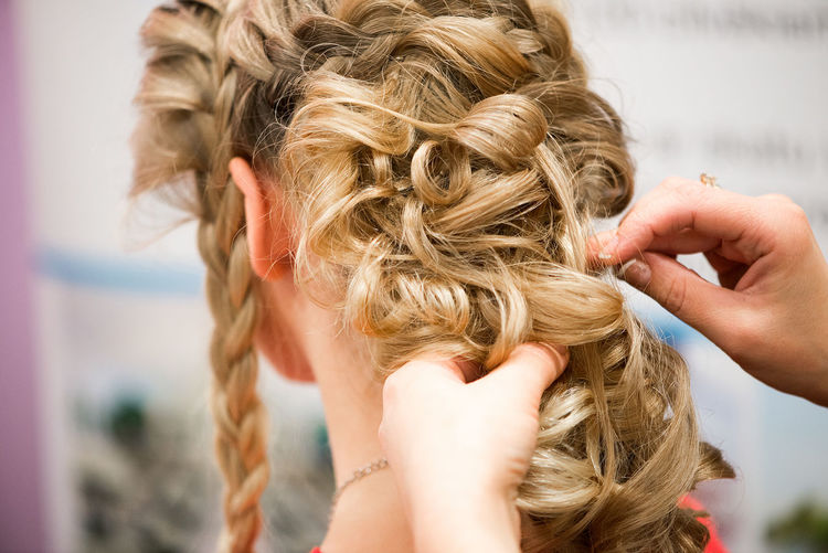 Close-Up Of Female Hairstylist Holding Blond Customers Hair At Salon