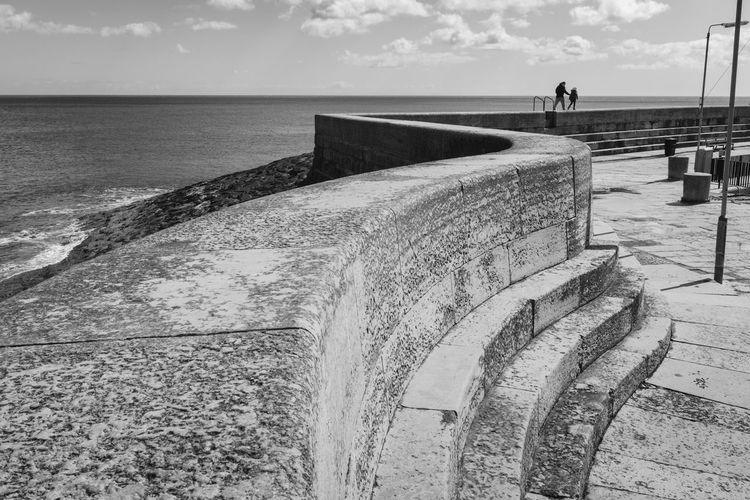 Retaining Wall By Sea Against Sky