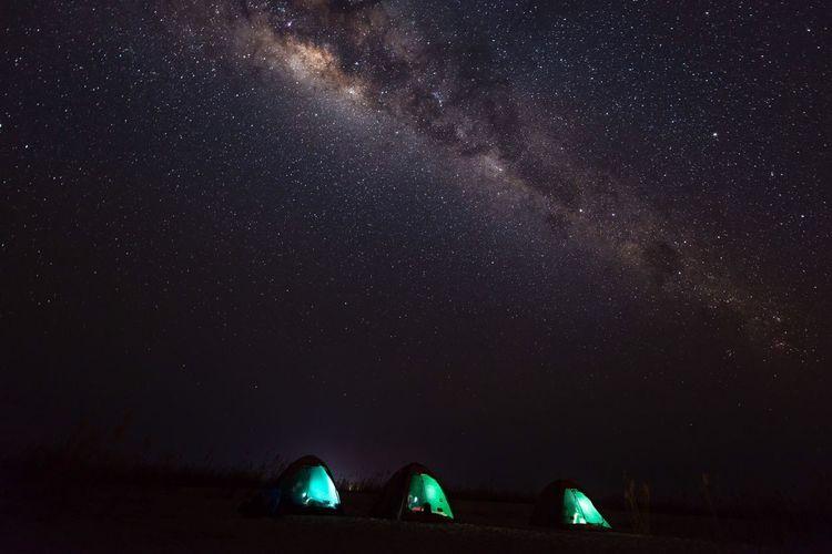 Illuminated tents on field against milky way at night