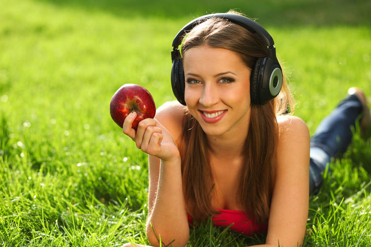 Woman with headphones listening music on the grass One Person Smiling Fruit Portrait Young Adult Grass Food Healthy Eating Apple - Fruit Women Young Women Food And Drink Plant Happiness Looking At Camera Wellbeing Adult Leisure Activity Beauty Beautiful Woman Hairstyle Hair Outdoors