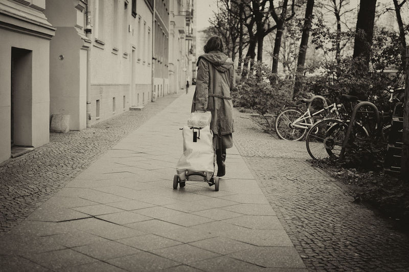 Rear view of woman walking on footpath with luggage cart