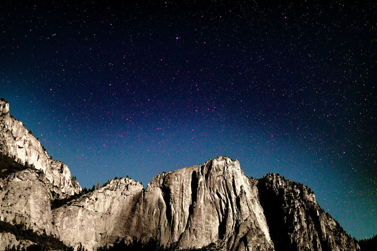 Low Angle View Of Rocky Mountains Against Starry Sky