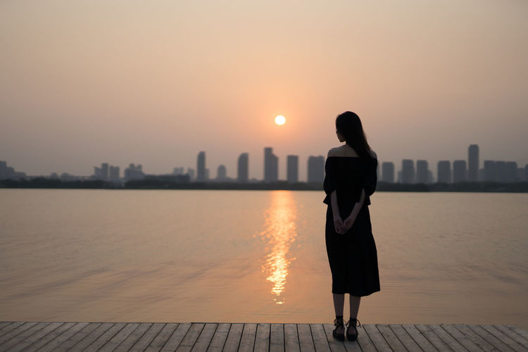 Rear view of woman standing on shore against sunset sky