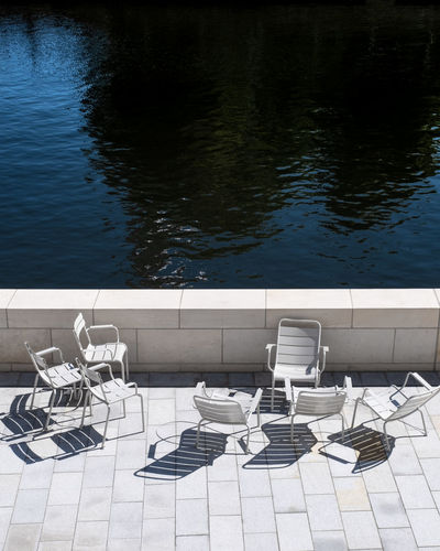 High angle view of chairs and table in swimming pool