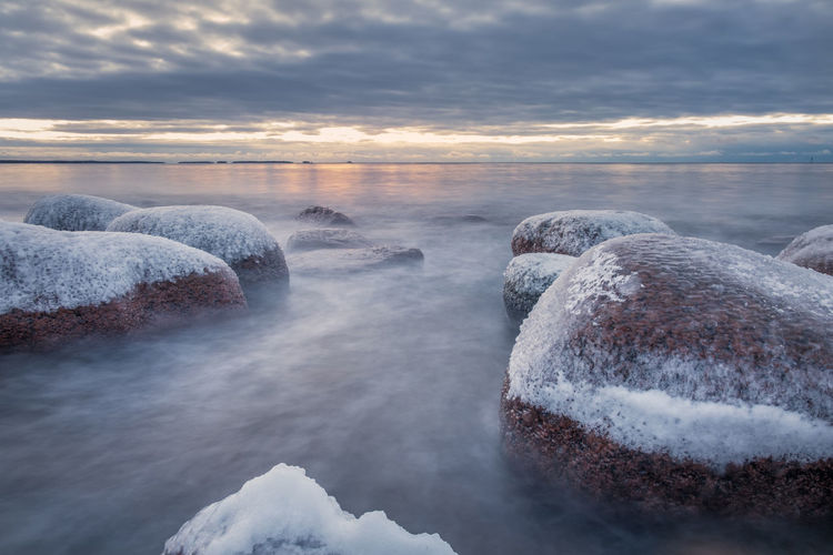 Snow covered rocks at beach against cloudy sky during sunset