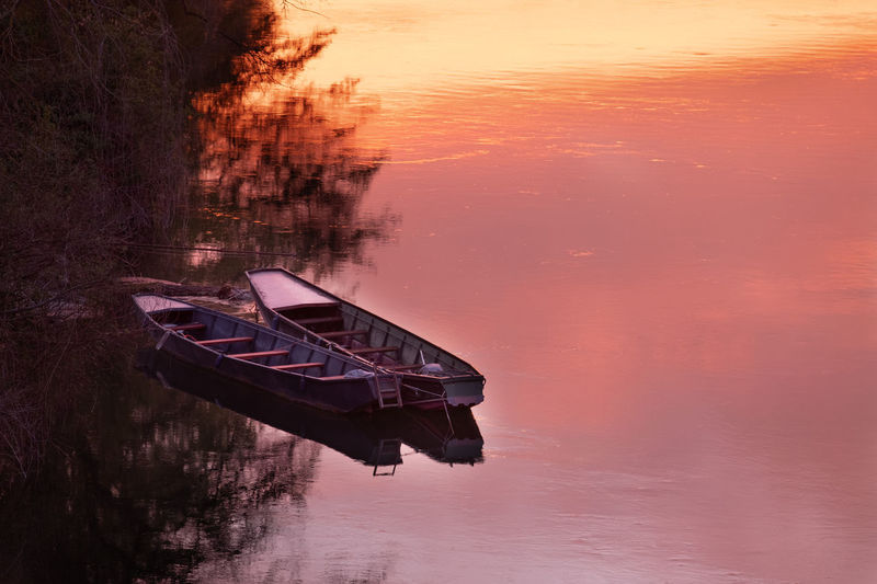 zwei Ruderboote am Rheinufer Water Nautical Vessel Reflection Sunset Transportation Waterfront Mode Of Transportation Tranquility Nature Sky Lake No People Beauty In Nature Tranquil Scene Orange Color Scenics - Nature Moored Tree Outdoors Sinking Rowboat Ruderboot