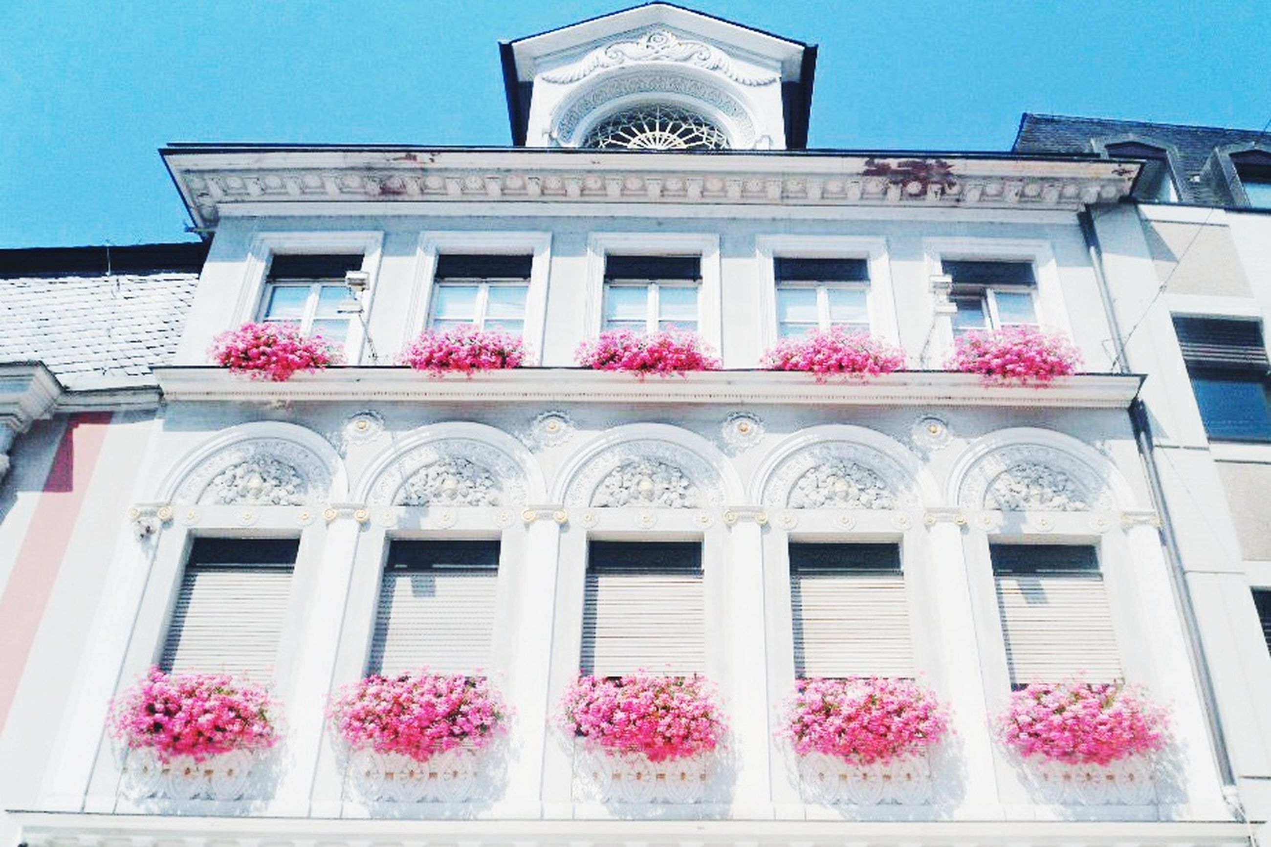 architecture, building exterior, built structure, low angle view, window, facade, sky, red, day, building, arch, outdoors, city, ornate, no people, clear sky, history, balcony, blue, sunlight