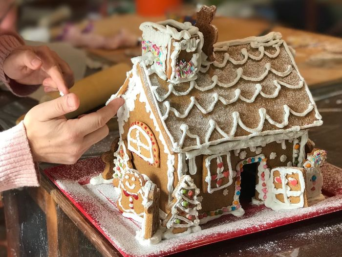 Building gingerbread house Cookies Wintertime Homemade Building Gingerbread House One Person Celebration Real People Sweet Food Human Body Part Human Hand Food Baked Creativity Christmas Hand Cake Moms & Dads