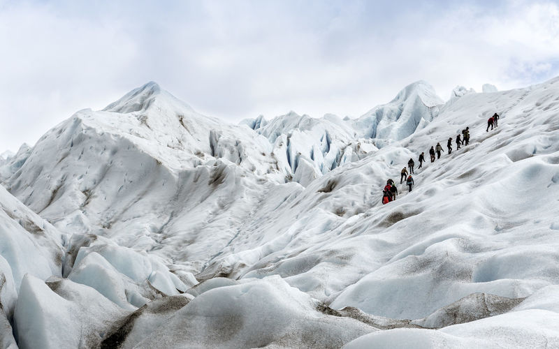 Low angle view of people climbing on glacier against sky
