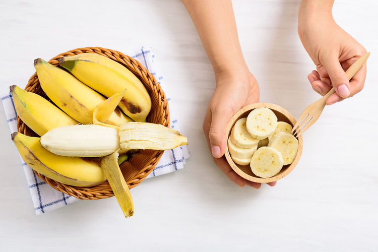 Hand holding fork for eating sliced banana in a bowl and peeled banana in a basket, top view Banana Basket Bowl Bunch Cuisine Diet Eating Food Fork Fresh Freshness Fruit Gourmet Hand Health Healthy Ingredient Natural Nature Nutrition Organic Peel Peeled Ripe Sliced Sweet Top View Tropical Vegetarian Vitamin Yellow Food And Drink Human Hand Indoors  Table High Angle View Healthy Eating Wellbeing Holding Ready-to-eat Breakfast