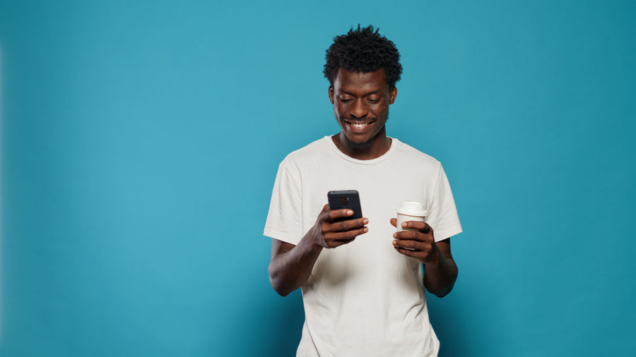 Young man using mobile phone against blue background