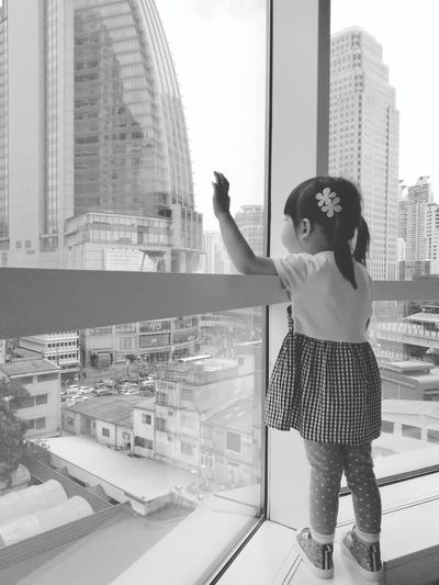 Full length of girl looking at city through glass window
