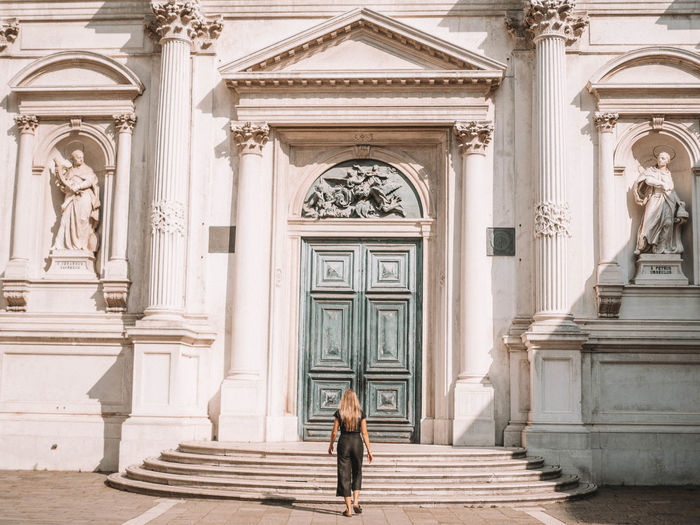 Full length of woman standing at entrance of historic building