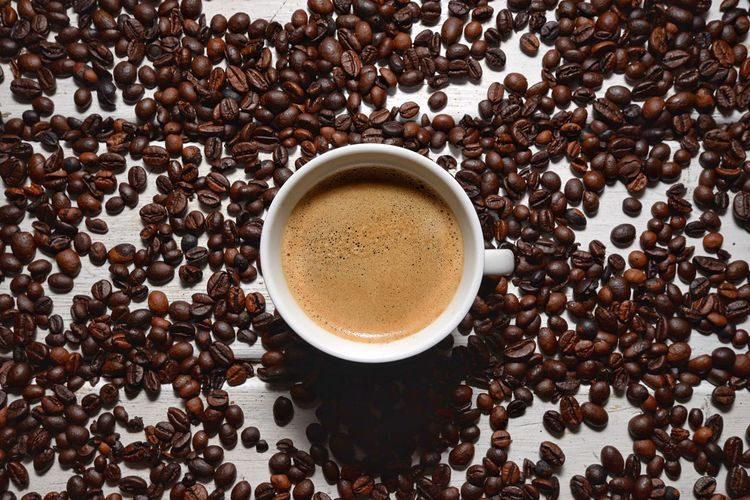 Directly Above Shot Of Coffee Cup With Beans On Table