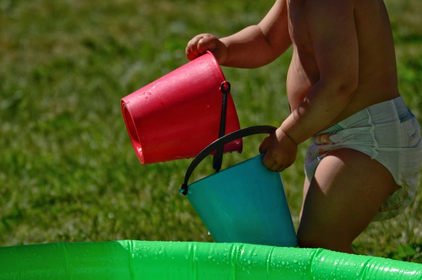 Childhood Family Wet Fun Sunlight Summer Pool Child One Person Real People Human Body Part Lifestyles Leisure Activity Day Focus On Foreground Grass Body Part Human Hand Outdoors Midsection Hand Holding