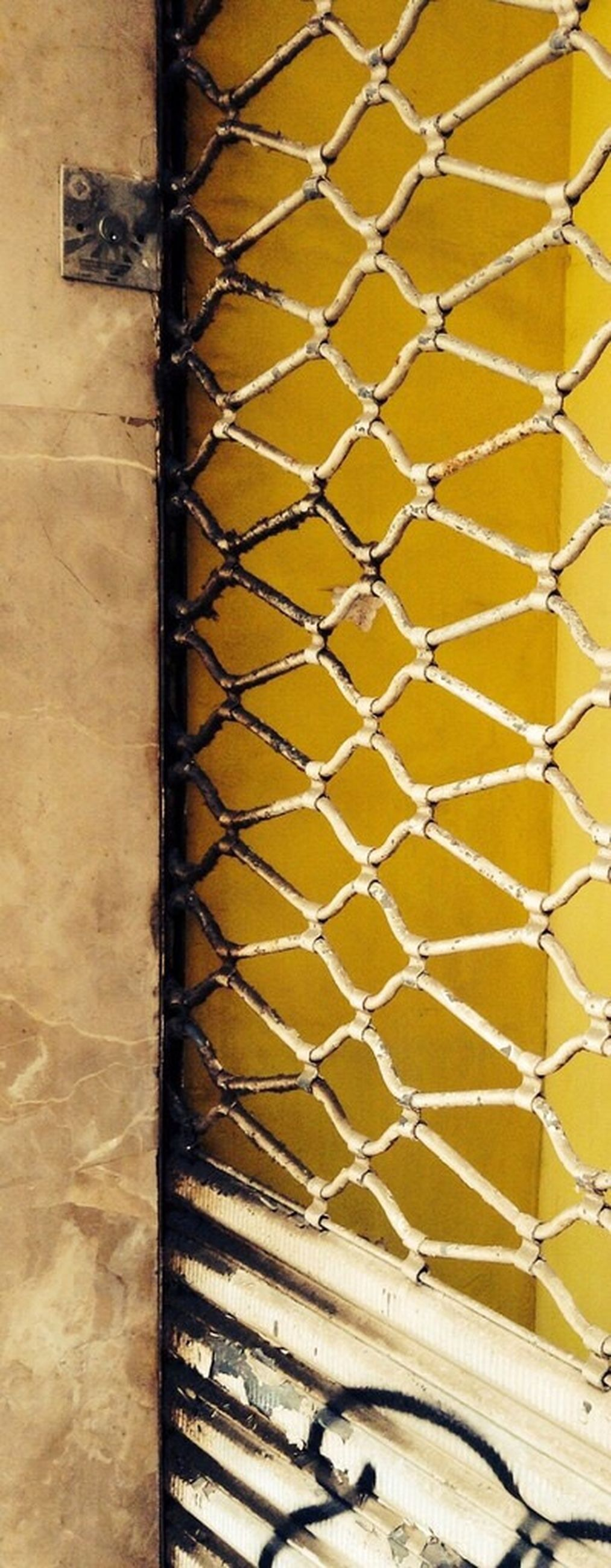 metal, pattern, wall - building feature, metallic, built structure, indoors, architecture, wall, full frame, textured, protection, close-up, no people, day, safety, sunlight, backgrounds, metal grate, brick wall