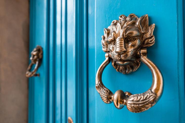 Close-up of door knocker on a blue door