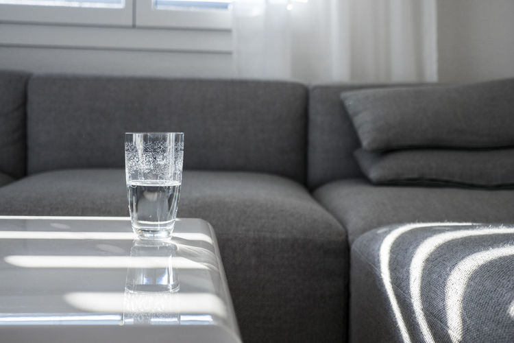 Glass with water on white table and furniture Autumn Clean Coffee Table Day Drink Drinking Glass Food And Drink Furniture Glass Glass - Material Home Interior Indoors  Living Room No People Sofa Switzerland Table