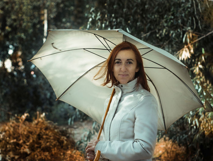 Portrait of woman with umbrella standing in forest