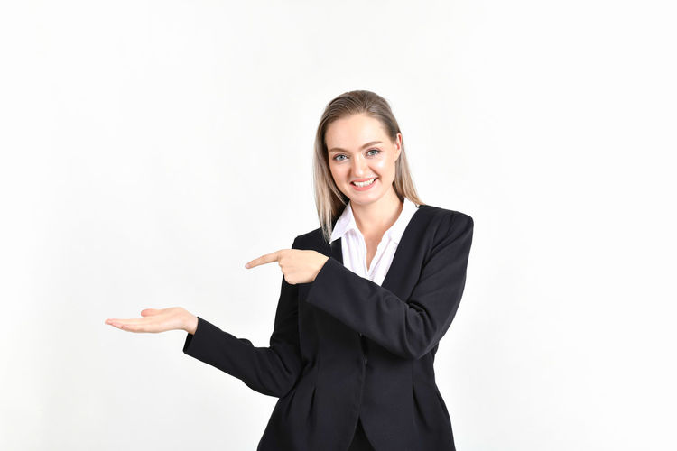 Portrait Of Smiling Businesswoman Gesturing Against White Background